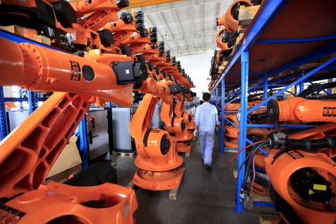 A worker walks past second-hand robots in a factory in Shanghai, August 21, 2015. More than a hundred second-hand robots used to make Audi A3s at a German car factory are going through refurbishment at a Wecan Group factory in Shanghai. Picture taken August 21, 2015. REUTERS/Aly Song  - GF10000184124