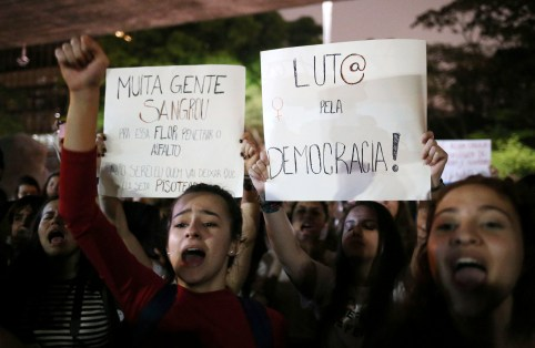 """Demonstrators shout slogans against Jair Bolsonaro, far-right lawmaker and presidential candidate of the Social Liberal Party (PSL), during a protest called """"dictatorship never again"""" in Sao Paulo, Brazil October 10, 2018. The poster (R) reads: """"Fight for democracy!"""" REUTERS/Amanda Perobelli - RC12E4A0D820"""