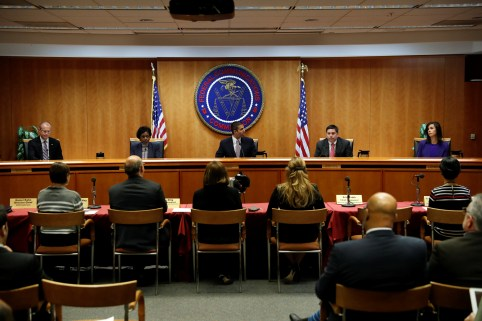 Chairman Ajit Pai (C) leads a vote on the repeal of so called net neutrality rules at the Federal Communications Commission in Washington, U.S., December 14, 2017. REUTERS/Aaron P. Bernstein - RC18AF078D70