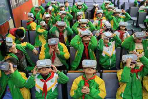 Primary school students wear virtual reality (VR) headsets inside a classroom in Xiangxi Tujia and Miao Autonomous Prefecture, Hunan province, China March 14, 2018. Picture taken March 14, 2018. REUTERS/Stringer  ATTENTION EDITORS - THIS IMAGE WAS PROVIDED BY A THIRD PARTY. CHINA OUT. - RC16E4321880