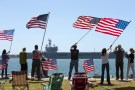 Supporters wave American flags along the shoreline as the USS Ronald Reagan, a Nimitz-class nuclear-powered super carrier, departs for Yokosuka, Japan from Naval Station North Island in San Diego, California  August 31, 2015. The Reagan is replacing the USS George Washington as part of a complicated three-carrier swap that exchanges crews for ships, saving the Navy millions in moving costs.  REUTERS/Mike Blake - GF10000188448
