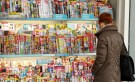 A woman looks at magazines displayed at a kiosk in Zurich March 16 , 2015. One of Switzerland's two big supermarkets, Coop, is to stop selling titles such as German magazine Der Spiegel, the German-language edition of Vogue and a Mickey Mouse comic because it says local distributors have not cut prices after a currency surge. The Swiss central bank's decision on Jan. 15 to end a cap on the value of the currency at 1.20 Swiss francs per euro sent the franc skyrocketing and led to fears for Switzerland's export-reliant economy. REUTERS/Arnd Wiegmann (SWITZERLAND - Tags: MEDIA BUSINESS) - GM1EB3H00BN01