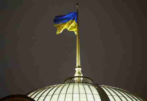 A Ukrainian national flag flies over the parliament building (Verkhovna Rada) during a parliament session to review a proposal by President Petro Poroshenko to introduce martial law for 60 days after Russia seized Ukrainian naval ships off the coast of Russia-annexed Crimea, in Kiev, Ukraine, November 26, 2018.  REUTERS/Gleb Garanich - RC1BD2505A10