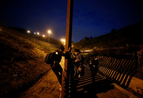 DATE IMPORTED:January 17, 2019Migrants from Honduras, part of a caravan of thousands from Central America trying to reach the United States, jump the fence to cross it illegally into San Diego County, U.S. (L), taken from the border wall in Tijuana, Mexico (R) January 16, 2019. REUTERS/Mohammed Salem