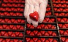 A worker displays a heart-shaped praline for Valentine's Day at a Wittamer chocolate boutique in Brussels February 14, 2012. REUTERS/Francois Lenoir (BELGIUM - Tags: FOOD SOCIETY) - GM1E82E1MJI01