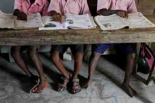 """Students from a primary school read books inside a classroom on Ghoramara Island, India, November 16, 2018. Ghoramara Island, part of the Sundarbans delta on the Bay of Bengal, has nearly halved in size over the past two decades, according to village elders. REUTERS/Rupak De Chowdhuri  SEARCH """"CHOWDHURI COASTLINE"""" FOR THIS STORY. SEARCH """"WIDER IMAGE"""" FOR ALL STORIES. - RC16F935BB30"""
