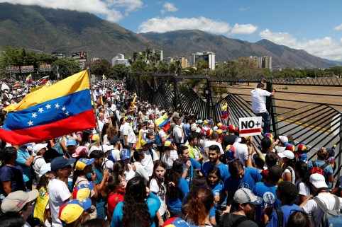 Supporters of the Venezuelan opposition leader Juan Guaido, who many nations have recognized as the country's rightful interim ruler, take part in a rally to demand President Nicolas Maduro to allow humanitarian aid to enter the country, outside of an Air Force base in Caracas, Venezuela February 23, 2019. REUTERS/Carlos Garcia Rawlins - RC1305D0E9B0
