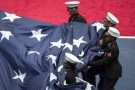 Members of the U.S. Marine Corps gather up a large U.S. flag before the Flavia Pennetta versus Roberta Vinci women's singles final match at the U.S. Open tennis tournament in New York, September 12, 2015. REUTERS/Carlo Allegri - GF10000203824