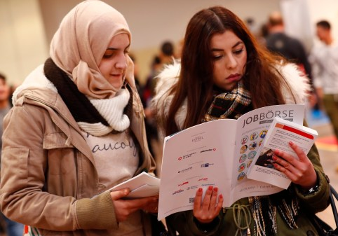 Two women visit the second job fair for migrants and refugees in Berlin, Germany, January 25, 2017.        REUTERS/Fabrizio Bensch - LR1ED1P0SO387