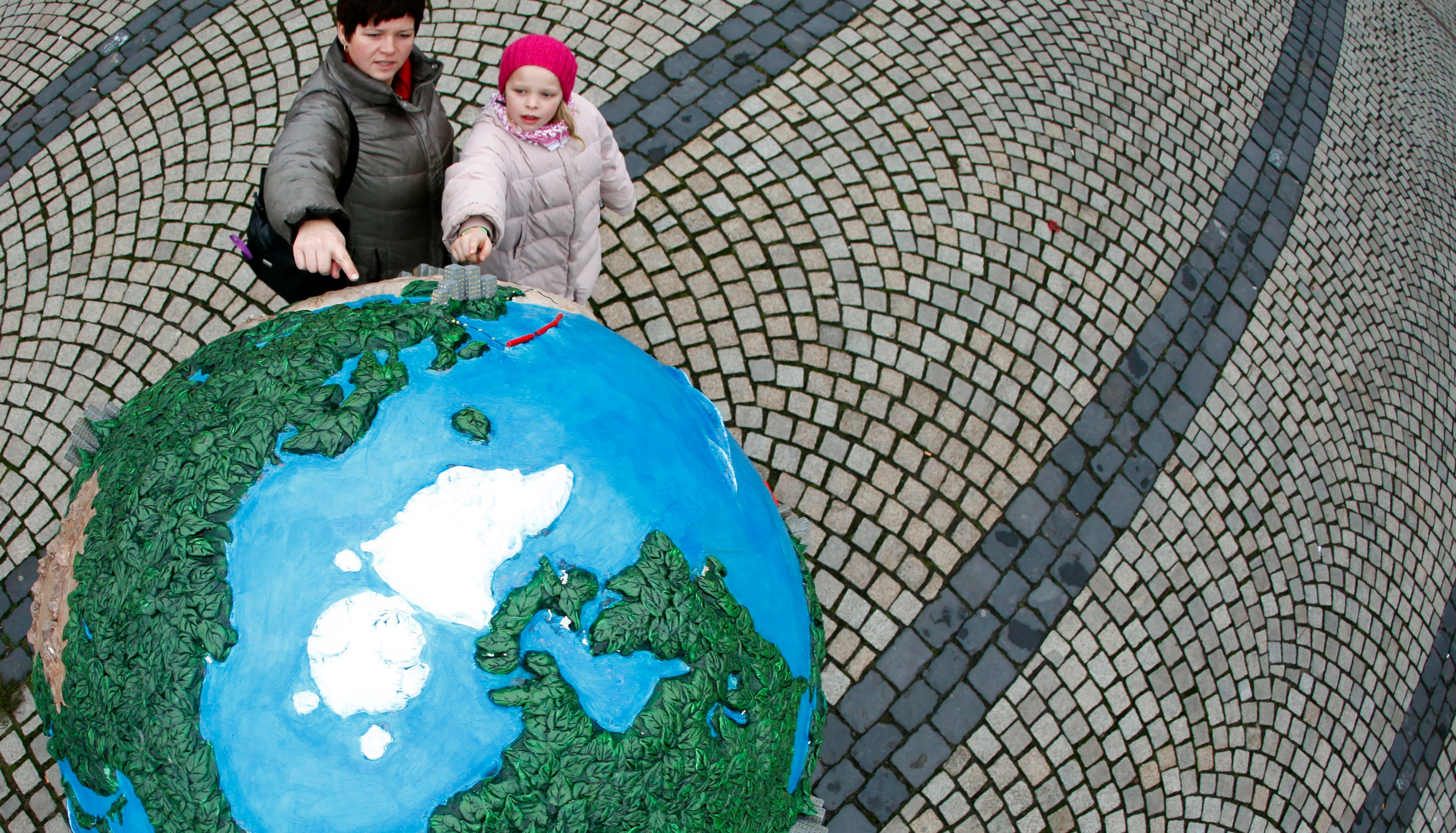 People look at a globe which is a part of of an installation in downtown Copenhagen December 6, 2009. Copenhagen is the host city for the United Nations Climate Change Conference 2009 which starts from December 7 until December 18.   REUTERS/Pawel Kopczynski  (DENMARK ENTERTAINMENT ENVIRONMENT IMAGES OF THE DAY) - GM1E5C61T3J01