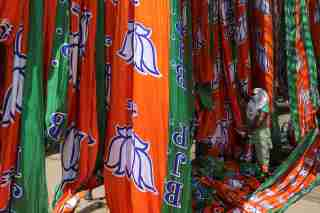 A worker pulls a roll of flags of India's ruling Bharatiya Janata Party (BJP) party kept for drying at a flag manufacturing factory, ahead of the 2019 general elections, in Ahmedabad, India, March 15, 2019. REUTERS/Amit Dave - RC120850C5B0