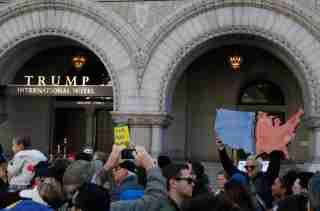 """A demonstrator protests with a sign showing a divided Red and Blue America in front of the Trump International Hotel during the """"March for Our Lives"""" event demanding gun control after recent school shootings at a rally in Washington, U.S., March 24, 2018. REUTERS/Leah Millis - HP1EE3O1FJKIW"""