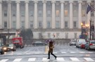 A woman crosses a nearly empty street at rush hour, near the U.S. Treasury Building during a snow storm in Washington March 5, 2015. A large winter storm reaching from Texas to southern New England, which prompted school closings and led to almost 2,300 flight cancellations, had dumped over a foot (30 cm) of snow on parts of the eastern United States by early Thursday morning. REUTERS/Joshua Roberts (UNITED STATES - Tags: ENVIRONMENT SOCIETY) - GM1EB351UKX01