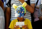 A boy plays Nintendo's game console prior to a parade where Pokemon's character Pikachu attends, in Yokohama, Japan, August 7, 2016. Picture taken on August 7, 2016. REUTERS/Kim Kyung-Hoon - S1AEUJDOXRAB