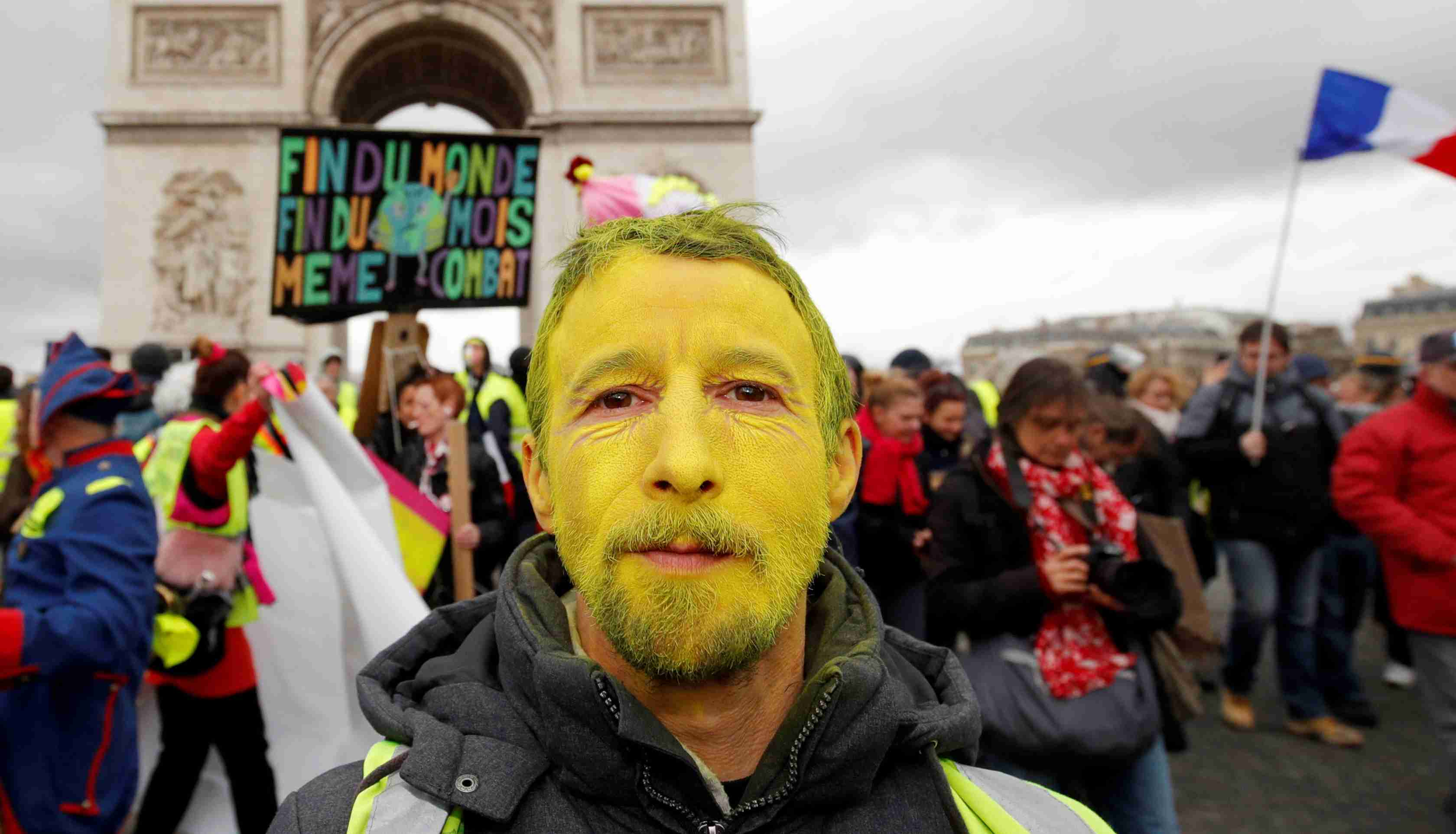 "A protester wearing a yellow vest and with his face painted yellow walks down the Champs Elysees during a demonstration by the ""yellow vests"" movement in Paris, France, march 9, 2019.  REUTERS/Philippe Wojazer - RC1B5A4470C0"