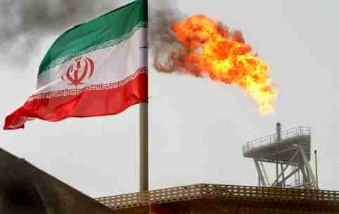 A gas flare on an oil production platform in the Soroush oil fields is seen alongside an Iranian flag in the Gulf July 25, 2005. REUTERS/Raheb Homavandi/File Photo - GF10000386922