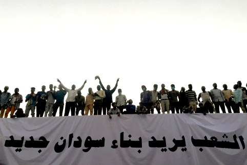"""Sudanese demonstrators stand next to a banner reading in Arabic """"People want to build new Sudan"""" as they chant slogans during a protest rally demanding Sudanese President Omar Al-Bashir to step down, outside Defence Ministry in Khartoum, Sudan April 9, 2019. REUTERS/Stringer - RC1BCDBB6200"""