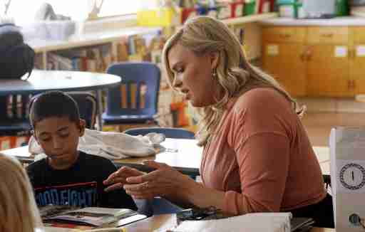 Kyle Schwartz (R), a 3rd grade teacher, works with student Chris Flores in her classroom at Doull Elementary School in Denver April 17, 2015. Schwartz, who posted notes from her third grade class online and started a social media whirlwind under the hashtag #WishMyTeacherKnew said on Friday the assignment had been a revelation for her.  REUTERS/Rick Wilking - GF10000063461