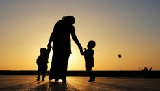 A woman walks with her two children at sunset near the seashore in Benghazi April 29, 2014. REUTERS/Esam Omran Al-Fetori (LIBYA - Tags: SOCIETY) - GM1EA4U0HMU01