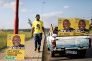 Musa Masina looks at election posters with the face of ANC president Cyril Ramaphosa, before hanging them on street poles in Soweto, South Africa, March 12, 2019. REUTERS/Siphiwe Sibeko - RC1E91576A50
