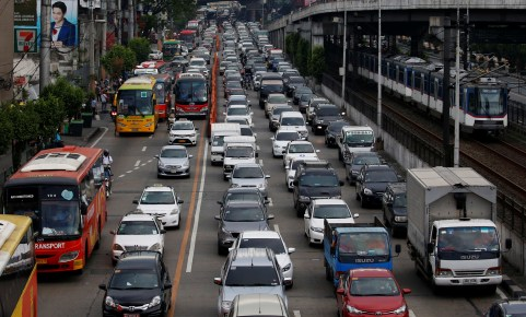 Motorists drive through a heavy traffic flow near a passing metro train along the main highway EDSA in Makati, Metro Manila, Philippines June 21, 2016. REUTERS/Erik De Castro - D1BETLELWXAA