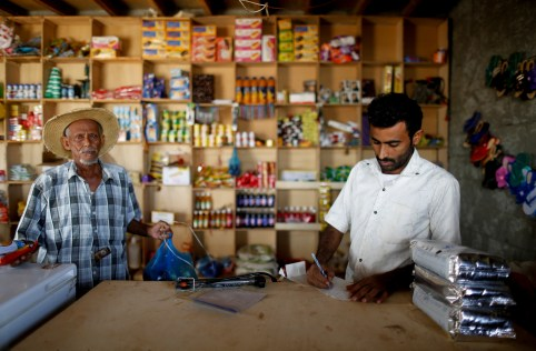 """A customer stands by as a vendor calculates at a shop near the village of al-Jaraib, in the northwestern province of Hajjah, Yemen, February 20, 2019. REUTERS/Khaled Abdullah     SEARCH """"YEMEN HUNGER"""" FOR THIS STORY. SEARCH """"WIDER IMAGE"""" FOR ALL STORIES. - RC18893184D0"""