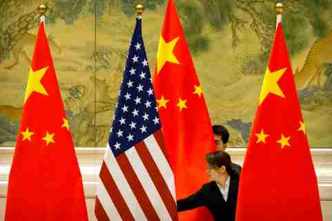 Chinese staffers adjust U.S. and Chinese flags before the opening session of trade negotiations between U.S. and Chinese trade representatives at the Diaoyutai State Guesthouse in Beijing, Thursday, Feb. 14, 2019. Mark Schiefelbein/Pool via REUTERS - RC16D7D1C040