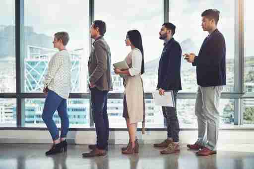 Shot of a group of businesspeople standing in line in an office