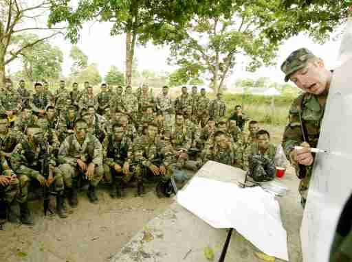 A U.S. Special Forces soldier talks to Colombian soldiers at a militarybase during training in Saravena, Arauca province, February 7, 2003. Atleast 70 U.S. soldiers are in Saravena training Colombian army troopsto combat leftist rebels. REUTERS/Eliana AponteEA/ME - RP3DRINWHOAA