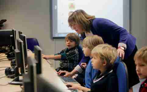 """Teacher Kristi Rahn (C) helps to first grade students during a computer lesson in school in Tallinn September 25, 2012. Estonian Tiger Leap Foundation has launched a program called """"ProgeTiiger"""" where Estonian students will be introduced to computer programming and creating web and mobile applications. According to representatives from the foundation, the program will start with students in the first grade, which starts around the age of 7, and will continue through a student's final years of public school, around age 15.  REUTERS/Ints Kalnins (ESTONIA - Tags: EDUCATION SCIENCE TECHNOLOGY) - GM1E89P1PG901"""