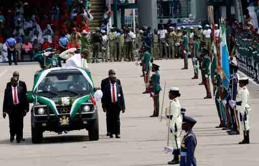 Nigeria's President Muhammadu Buhari bows before the flags of the various military formations during his inspection of the a celebration marking the new Democracy Day, a national holiday in honour of late M.K.O Abiola in Abuja, Nigeria June 12, 2019 REUTERS/Afolabi Sotunde - RC1DEE281A60
