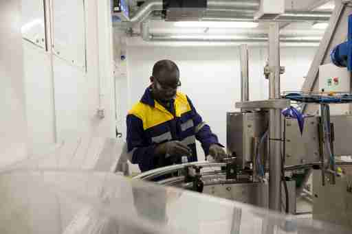 A technician inspects newly moulded bottles at the Guinness pop-up plant in Accra, July 2, 2014. Picture taken July 2, 2014.  To match Insight CONSUMERS-MANUFACTURERS/AFRICA    REUTERS/Francis Kokoroko (GHANA - Tags: BUSINESS) - GM1EA7411EN01