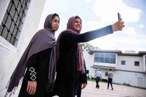 Two Muslim women take pictures after the first Friday prayers during the month of Ramadan at Diyanet Center of America in Lanham, Maryland, U.S., May 10, 2019. REUTERS/Amr Alfiky - RC15CA4BC8D0