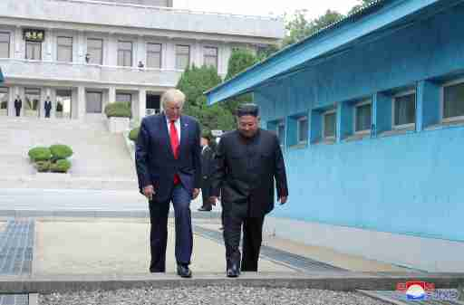 U.S. President Donald Trump and North Korean leader Kim Jong Un cross over a military demarcation line at the demilitarized zone (DMZ) separating the two Koreas, in Panmunjom, South Korea, June 30, 2019. KCNA via REUTERS    ATTENTION EDITORS - THIS IMAGE WAS PROVIDED BY A THIRD PARTY. REUTERS IS UNABLE TO INDEPENDENTLY VERIFY THIS IMAGE. NO THIRD PARTY SALES. SOUTH KOREA OUT. NO COMMERCIAL OR EDITORIAL SALES IN SOUTH KOREA. - RC1D4113FE00