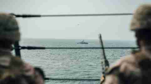 U.S. Marines observe an Iranian fast attack craft from USS John P. Murtha during a Strait of Hormuz transit, Arabian Sea off Oman, in this picture released on July 18, 2019. Donald Holbert/U.S. Navy/Handout via REUTERS ATTENTION EDITORS- THIS IMAGE HAS BEEN SUPPLIED BY A THIRD PARTY. - RC1FF5621490