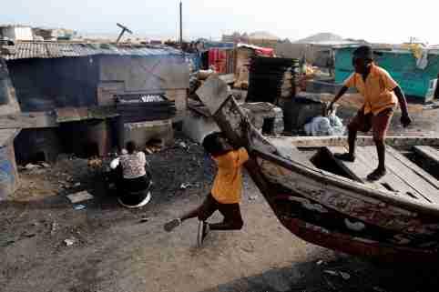 Boys play as a woman prepares smoked fish in Jamestown in Accra, Ghana November 28, 2018. REUTERS/Zohra Bensemra - RC178F9FF100