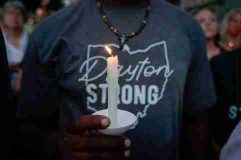 A mourner holds a candle during a vigil at scene of a mass shooting in Dayton