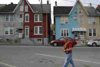"A man walks past multi-colored homes that face the now-closed Bethlehem Steel mill in Bethlehem, Pennsylvania, U.S. April 22, 2016. After Bethlehem Steel's blast furnaces went silent 20 years ago in the city of Bethlehem, Pennsylvania, the local economy bounced back as new industrial parks filled with e-commerce companies and white-collar businesses fleeing New York's higher costs. That adds to the challenge for Donald Trump, Republican nominee for the U.S. presidency, as he seeks voters' backing in the state's primary on April 26. REUTERS/Brian Snyder SEARCH ""BETHLEHEM STEEL"" FOR THIS STORY. SEARCH ""THE WIDER IMAGE"" FOR ALL STORIES - GF10000393653"