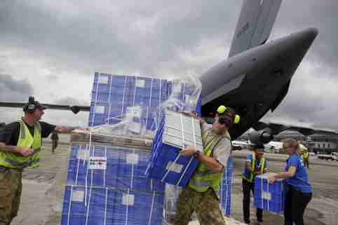 Air crew and volunteers unload aid from a Royal Australian Air Force (RAAF) transport plane carrying donated aid for Myanmar's flood victims at Yangon international airport in Yangon on August 10, 2015. REUTERS/Soe Zeya Tun - GF20000018961