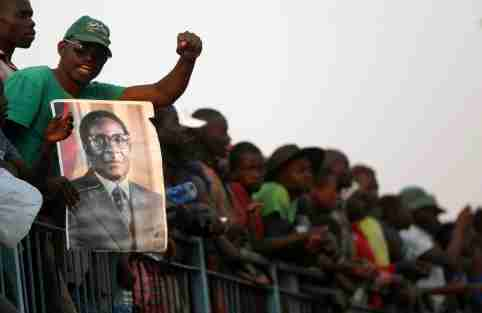 A mourner holds a poster of Robert Mugabe during the viewing of his body