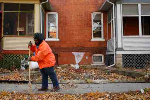 Ardana McFerren sweeps leafs outside of her home in the historic Pullman neighborhood in Chicago November 20, 2014. U.S. President Barack Obama is expected to announce the designation of the Pullman neighborhood as a national park on February 19, according to park advocates. The neighborhood's brick homes and ornate public buildings were built in the 1800s by industrialist George Pullman as a blue-collar utopia to house workers from his sleeper car factory. Picture taken November 20, 2014.  REUTERS/Andrew Nelles (UNITED STATES - Tags: SOCIETY ENVIRONMENT POLITICS) - TM3EABN1EN701