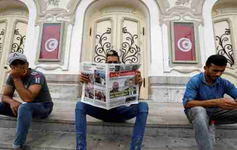 A man reads a local newspaper displaying pictures of two candidates for the second round of Tunisia's presidential election, in Tunis, Tunisia September 18, 2019. REUTERS/Zoubeir Souissi - RC1B2D4B94C0