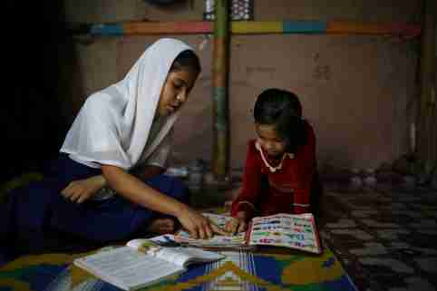 Yasmin, a Rohingya girl who was expelled from Leda High School for being a Rohingya, helps her younger sister to study in Leda camp in Teknaf, Bangladesh, March 5, 2019. REUTERS/Mohammad Ponir Hossain - RC14D96237D0