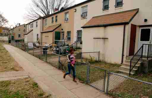 A woman walks on a path in the Berry Farm housing project in Ward 8 of Washington November 20, 2012. Picture taken November 20, 2012. To match Special Report EQUALITY/WASHINGTON  REUTERS/Kevin Lamarque  (UNITED STATES - Tags: SOCIETY BUSINESS EMPLOYMENT POVERTY) - GM1E8CI1MCM01