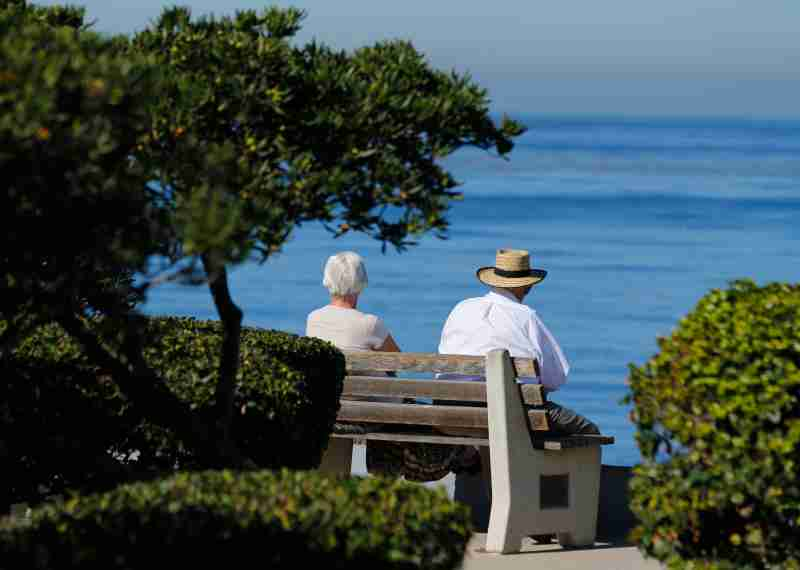 An elderly couple looks out at the ocean as they sit on a park bench in La Jolla, California November 13, 2013.   REUTERS/Mike Blake  (UNITED STATES - Tags: SOCIETY ENVIRONMENT) - GM1E9BE0E8L01