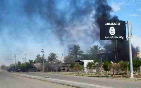 Smoke raises behind an Islamic State flag after Iraqi security forces and Shiite fighters took control of Saadiya in Diyala province from Islamist State militants, November 24, 2014. Iraqi forces said on Sunday they retook two towns north of Baghdad from Islamic State fighters, driving them from strongholds they had held for months and clearing a main road from the capital to Iran. There was no independent confirmation that the army, Shi'ite militia and Kurdish peshmerga forces had completely retaken Jalawla and Saadiya, about 115 km (70 miles) northeast of Baghdad. Many residents fled the violence long ago. At least 23 peshmerga and militia fighters were killed and dozens were wounded in Sunday's fighting, medical and army sources said.  REUTERS/Stringer (IRAQ - Tags: CIVIL UNREST CONFLICT MILITARY TPX IMAGES OF THE DAY) - GM1EABP0BT301