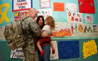 A military family reunites at DFW airport in Dallas, Texas, October 22, 2008. Among those struggling in the worst financial crisis since the Great Depression are members of the U.S. armed forces and their families. Picture taken October 22, 2008. To match feature FINANCIAL/MILITARY REUTERS/Jessica Rinaldi (UNITED STATES) - GM1E4AS1CUD01