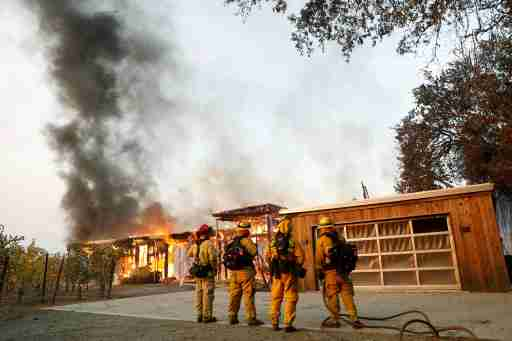 A group of firefighters look on as a house burns during the wind-driven Kincade Fire in Healdsburg, California, U.S. October 27, 2019. REUTERS/Stephen Lam - RC1CE4C5F940