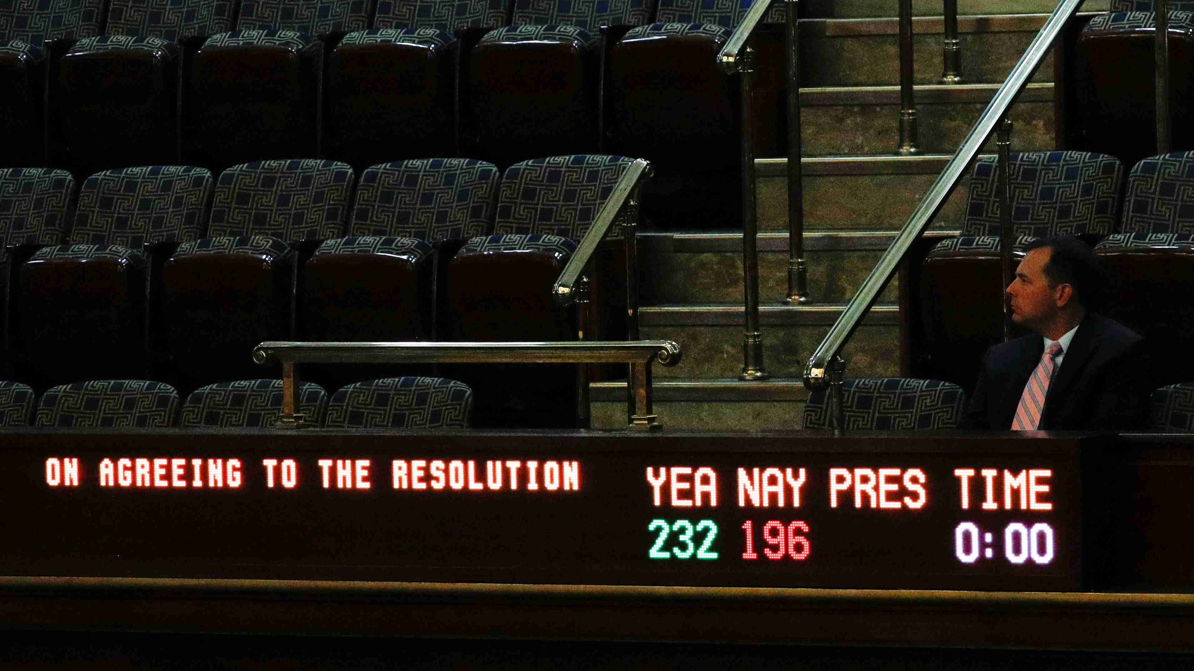 A man sits in the visitors gallery above the floor of the U.S. House of Representatives as a display board shows the final vote tallies of 232 Yea and 196 Nay on a resolution that outlines the next steps in the impeachment inquiry of U.S. President Donald Trump on Capitol Hill in Washington, U.S., October 31, 2019. REUTERS/Tom Brenner - RC1125BB6970