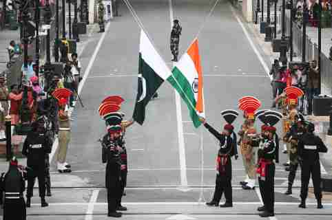 Pakistani Rangers (wearing black uniforms) and Indian Border Security Force (BSF) officers lower their national flags during parade on the Pakistan's 72nd Independence Day, at the Pakistan-India joint check-post at Wagah border, near Lahore, Pakistan August 14, 2019. REUTERS/Mohsin Raza - RC14044E1270
